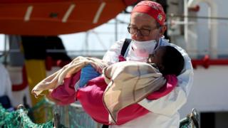 "A doctor carries a child as migrants disembark from the MSF vessel at Pozzallo""s harbour in Sicily, Italy, 25 April 2016"