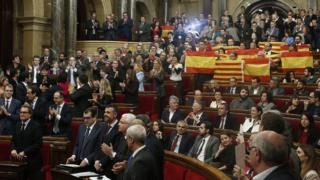 Popular Party of Catalonia members, right, show Spanish flags and Catalonia flags at the end of a parliamentary session at the parliament in Barcelona
