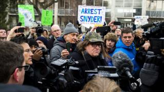 Flint, Michigan, native and filmmaker Michael Moore attends a rally outside city hall in Flint on 16 January 2016