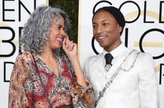 Musician Pharrell Williams (right) and producer Mimi Valdes arrive at the 74th annual Golden Globe Awards