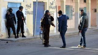 Tunisian police officers take positions during clashes with militants in Ben Guerdane