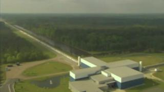 An aerial view of the LIGO experiment in Louisiana. You can see both of the laser beam pipes heading off from the main building.