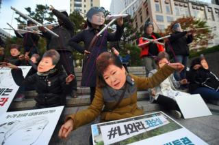 Protesters wearing masks of South Korean President Park Geun-Hye (front) and her confidante Choi Soon-Sil (back) pose as though the latter is a puppet master for the former, at a protest in Seoul on 29 October 2016.