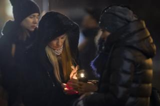Women try to light a candle to place with flowers in front of the Alexandrov Ensemble building in Moscow, Russia, Monday, 26 December
