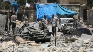 Syrian men inspect damage after air strikes on rebel-held Mashhad district of Aleppo (13 June 2016)