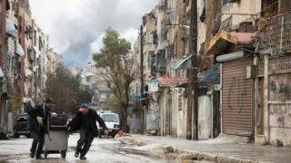 Smoke is seen billowing in the background on December 14, 2016 in this picture taken in a rebel-held neighbourhood in the northern city of Aleppo