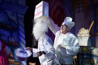 """Darren Hart (Ikoboo, L) is covered with """"flour"""" by Tony Whittle (King Eric) during a performance of the traditional pantomime """"Sleeping Beauty"""" at the Hackney Empire"""