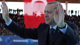 Turkey's President Recep Tayyip Erdogan salutes as he arrives to attend a ceremony marking the 102nd anniversary of Gallipoli campaign, in the Aegean port of Canakkale, near Gallipoli
