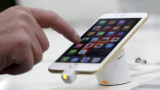 A man tests a mobile phone, an iPhone 6 by Apple in a shop in Munich, Germany, 27 January 2016.
