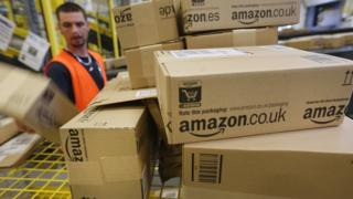 Amazon branded cardboard boxes being handled in one of the online retailers warehouses