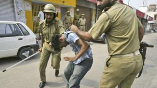 File photo - policemen beat a protester during a curfew in Jammu, India, on July 2, 2008.
