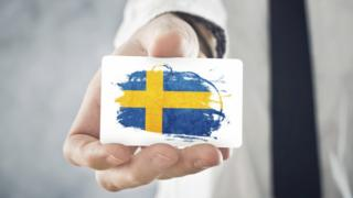 Man holding business card with Swedish flag