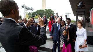 Barack Obama, left, takes a photo on a smartphone of a family with George W Bush, at a formal event.