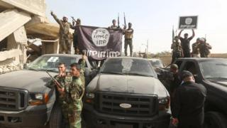 Shia militiamen hold an Islamic State group flag upside down after capturing Saqlawiya, outside Falluja (4 June 2016)