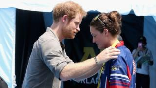 Prince Harry presents Elizabeth Marks with her medal