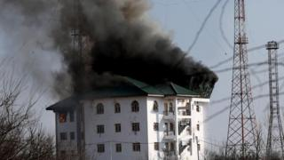 Smoke billows from a building where suspected militants have taken refuge during a gun battle on the outskirts of Srinagar (21 February 2016)