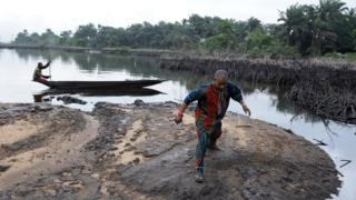 A man walks on slippery spilled crude oil on the shores and in the waters of the Niger Delta swamps of Bodo,