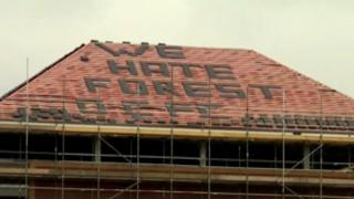 """We hate Forest"" on roof of building on A50"