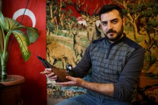 Ismail Ozbek, 23, poses for a photograph with one of his pigeons in Sanliurfa, Turkey