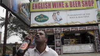 A man takes a swig of Kingfisher beer outside a liquor store