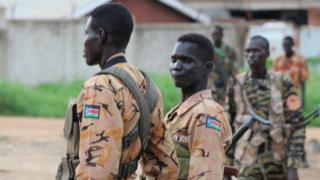 "South Sudanese policemen and soldiers stand guard along a street following renewed fighting in South Sudan""s capital Juba, July 10, 2016"