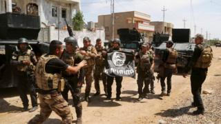 Iraqi troops hold Islamic State flag upside down inside town of Hit on 13 April 2016