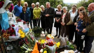 People look at floral tributes left at the scene of the fire