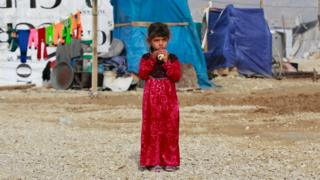 A Syrian girl eats a sandwich as she stands outside her family tent, during the visit of Filippo Grandi, the United Nations High Commissioner for Refugees, UNHCR, to a Syrian refugee camp in the town of Saadnayel, in the Bekaa valley, east Lebanon, Friday, Jan. 22, 2016.