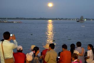 "Cambodian people watch as the ""supermoon"" rises over the Mekong river in front of the Royal Palace in Phnom Penh on November 14, 2016"