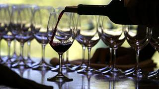 Red wine being poured into glasses