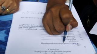 A person fills out their voter registration form in preparation for upcoming general elections, in Mandalay, Myanmar, 08 July 2015