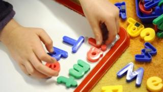 Primary school child, working in class with plastic letters