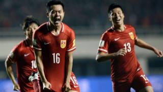 Huang Bowen (C) of China celebrates with his teammates after scoring against Qatar on March 29, 2016