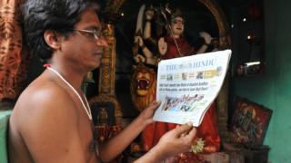 Indian Hindu priest Krishnama Charyulu reads a newspaper with the high court verdict of disputed Ayodhya case inside the temple in Hyderabad on October 1, 2010.