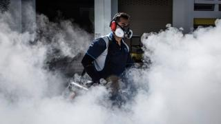 A pest control worker fumigates the grounds of a apartment block in Aljunied on 3 September 2016 in Singapore.