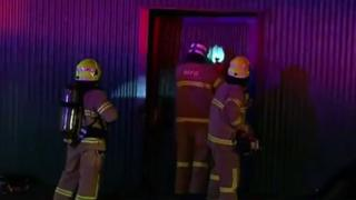 Firefighters force their way into the factory in Melbourne