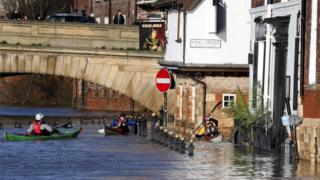 Canoeists check out buildings in flooded York on December 31, 2015