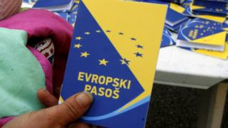 A volunteer holds up a mock European passport during a campaign by the Centre for Promotion of Civil Society in Sarajevo - 2010