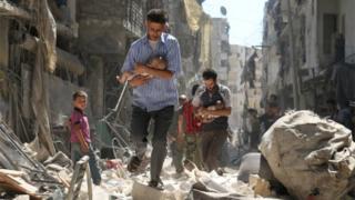 Syrian men carry babies through rubble in Salihin neighbourhood of Aleppo (September 2016)