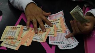 A woman picks up her Powerball lottery tickets in Hawthorne, California. Photo: 13 January 2015