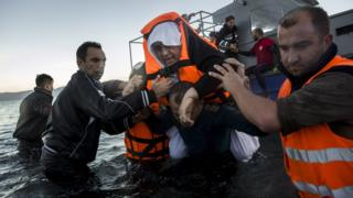 Volunteers help an elderly woman on the coast of Lesbos (1 Dec)