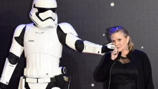 Carrie Fisher poses next to a Stormtrooper at a film premier