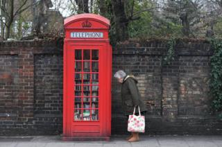 A woman looks at books in a decommissioned red telephone box in London