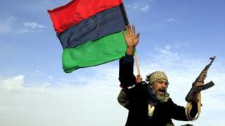 A rebel soldier gestures atop a car as he heads to Brega, in Ajdabiya March 2, 2011.