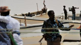Armed militiamen and some pirates stand among fishing boats on the coast in the central Somali town of Hobyo on August 20, 2010.