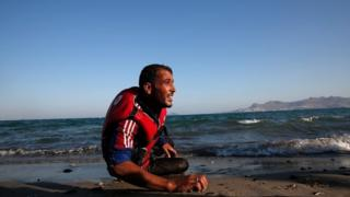 A migrant from Syria rests on the beach in Kos, Greece (29 Aug 2015)