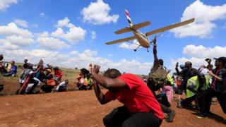 Spectators react as a plane flies over them during the Vintage Air Rally at the Nairobi National Park in Kenya - Sunday 27 November 2016