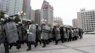 Armed paramilitary policemen run in formation during a gathering to mobilize security operations in Urumqi, Xinjiang Uighur Autonomous Region, in this June 29, 2013