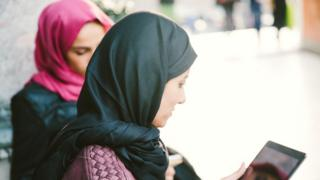 Women in hijab looking at a tablet (stock image)