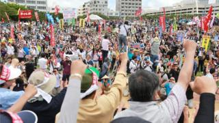 Hundreds of protesters shout slogans and raise fists during a demonstration in Naha on 15 May 2016 - the 44th anniversary of the islands' reversion from US control - against the construction of a US Marine Corps air base in Nago's Henoko district